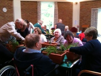 "Planting herbs into containers with the help of ""Thrive"" gardening for the disabled."